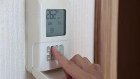 Imagens de vídeo da mão da mulher usando um controlo a distância para girar sobre em casa o condicionador de ar vídeos de arquivo