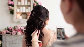 Imagens do cabeleireiro de um penteado do casamento no telefone vídeos de arquivo
