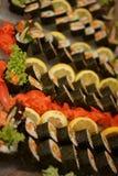 Imagens dos pratos frescos do sushi com uma grande variedade decorados com limão e o gengibre colorido com folhas da alface Foco  imagem de stock