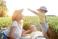 Imagens ensolaradas de uma família feliz com uma criança pequena Os pais e o filho descansam fora da cidade no ar livre Fotos de Stock