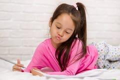 Images de dessin mignonnes de petite fille tout en se trouvant sur le lit photos stock