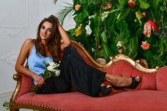 Free Images Of Beautiful Glamorous Girl On The Retro Red Couch And Wall With Green Leaves And Flowers Stock Image - 155222171
