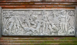 Images of people and dogs carved on a stone plate. Indonesia, Bali Island Royalty Free Stock Photo