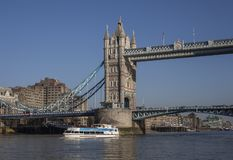Tower Bridge and the river Thames; sunny day and shiny waters of the river. This images shows the Tower Bridge.Tower Bridge is a combined bascule and suspension stock photo