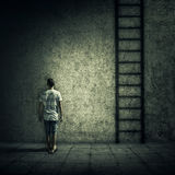 Imaginary escape. Abstract idea with a person standing in a dark room, in front of a concrete wall, figuring a ladder to escape. Surrounded by limitations, daily stock image