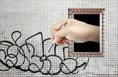Imaginary grafitti. A hand from a picture frame reaching out to scribble a grafitti on the wall stock photo