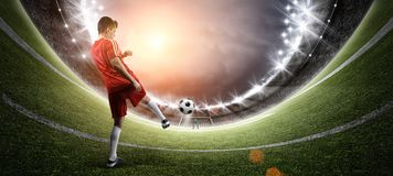 Football player in the stadium. The imaginary soccer stadium is modelled and rendered Stock Images