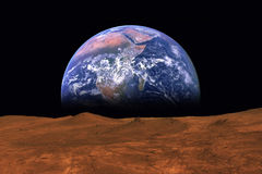 Imaginary view of earth rising from the horizon of plant Mars Royalty Free Stock Photos