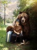 Imagination Boy and Brown Bear on Nature Trail. A young boy is sitting on a nature trail in the woods with a suitcase and book with a bear animal behind him for Royalty Free Stock Image