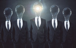 Imagination concept. Glowing lamp headed businessmen on chalkboard background. Imagination concept stock photography
