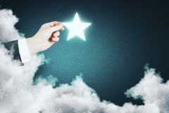 Imagination concept. Hand holding glowing star on abstract blue background with cloud. Imagination concept Royalty Free Stock Image