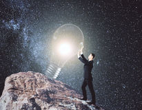 Imagination concept. Side view of young businessman on rock hill holding glowing light bulb. Space background. Imagination concept. 3D Rendering royalty free stock photos
