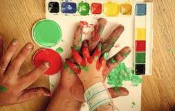 Imagination, créativité et liberté Mains dessinant avec les peintures et la palette multicolore sur le livre blanc Photo stock