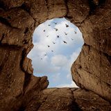 Imagination And Discovery Concept. As a rocky cliff with an opening on top shaped as a human head as a new life metaphor and success motivation symbol with a Royalty Free Stock Photos