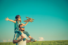 Imagination and freedom concept. Happy child playing with father outdoors. Family having fun in summer field. Travel and vacation concept. Imagination and Stock Photography