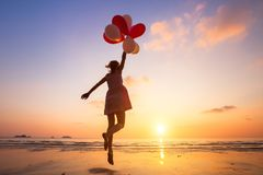 Imagination, happy girl jumping with multicolored balloons. At sunset on the beach, fly, follow your dream stock image