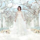 Imagination. Mariage. Jeune mariée dans la robe blanche au-dessus des arbres et des flocons de neige congelés d'hiver Photo libre de droits