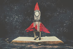 Imagination is a space of learning fun. Creative reading concept on a retro toy rocket landing on a kids book when imagination is a space of learning fun Stock Images