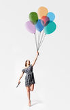 Imagination. Young woman is flying away with bunch of balloons Royalty Free Stock Image