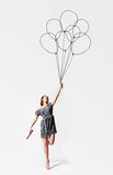 Imagination. Young woman is flying away with drawn balloons Royalty Free Stock Images