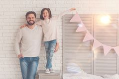 Imaginative family preparing a surprise together. Team of a dream. Adventurous sincere lovely daughter and dad having fun in a living room while hanging cute stock photo