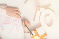 Imaginative gifted child making a surprise for mom. Persistent little artist. Lively sincere inventive girl working on pretty greeting card while drawing it by Royalty Free Stock Photography