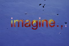 Imagine. A small section of a piece of graffiti on a blue painted wall that says imagine in mulit-colored paint Stock Photos