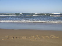 Imagine. Written on the sand beside the ocean Royalty Free Stock Photography