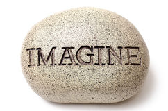 Imagine engraved on a rock. Creek pebble with the word imagine carved in stone Stock Images