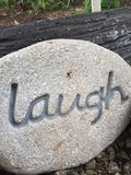 Laugh. Inspirational thoughts, positive quotes, creative, rock, pebble, unique, personalised, laugh garden ornament display Stock Image