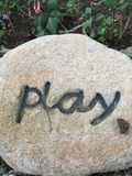 Play. Inspirational thoughts, positive quotes, creative, rock, pebble, unique, personalized, play Stock Photography