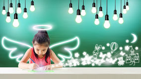 Imagine of little angel drawing her dream happiness. With wings Royalty Free Stock Photos