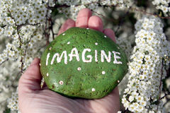 Imagine Rock. Hand holding a rock with the words IMAGINE painted on it in front of a flowering bush Royalty Free Stock Photos