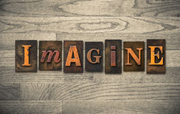 Imagine Wooden Letterpress Theme. The word IMAGINE theme written in vintage, ink stained, wooden letterpress type on a wood grained background Royalty Free Stock Photos