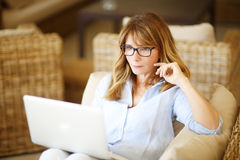 Imagining all the possibilities. Close-up portrait of casual woman using her laptop while sitting on couch and working Royalty Free Stock Photo