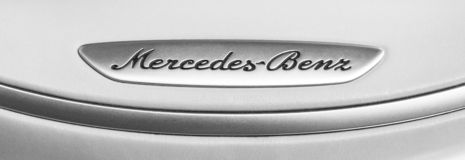 Close up view of a Mercedes-Benz logo on white leather steering wheel. Modern car interior details. Black and white royalty free stock photos