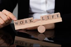 An Imbalance Between Life And Work On Seesaw. Close-up Of A Person Showing Imbalance Between Life And Work On Seesaw stock photography