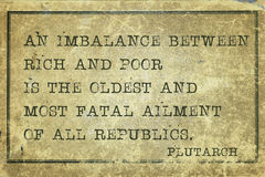 Imbalance Plutarch. An imbalance between rich and poor - ancient Greek philosopher Plutarch quote printed on grunge vintage cardboard royalty free stock images