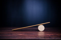 Imbalance scale. On wooden board stock image