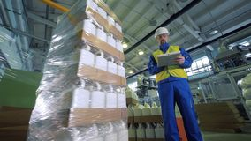 Imballaggio automatico delle scatole metalliche di plastica e di un lavoratore che lo controlla stock footage