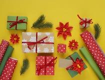 Imballaggio del regalo del ` s del nuovo anno Fondo giallo Molti contenitori di regalo legati con i nastri Abete b Immagine Stock
