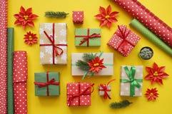 Imballaggio del regalo del ` s del nuovo anno Fondo giallo Molti contenitori di regalo legati con i nastri Abete b Immagini Stock