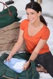 Imballaggio della donna il suo sacchetto Fotografie Stock Libere da Diritti