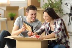 Imballaggio delle coppie mentre muovendo casa fotografia stock