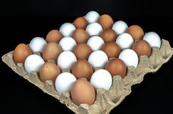 Imballaggio delle uova gialle e bianche del pollo sistemate in una composizione diagonale su un fondo nero fotografia stock
