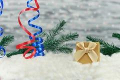 Imballaggio festivo del contenitore di regalo con l'arco di colore dell'oro su neve bianca Immagini Stock