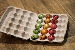 Imballaggio incompleto delle uova colorate Vista laterale ingrassare un pavimento di legno fotografia stock libera da diritti