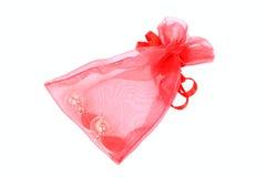 Imballaggio trasparente rosso con gli orecchini all'interno Fotografie Stock