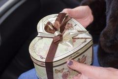 Imballato con un regalo nelle mani delle donne Fotografia Stock