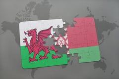 imbarazzi con la bandiera nazionale del Galles e della Bielorussia su un fondo della mappa di mondo Fotografie Stock